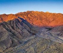 Mountain range with the sunset shining on it.