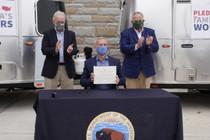 Three men next to RV's who signed a pledge.