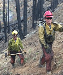 Two firefighters walking up a hill.