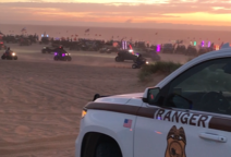 A BLM Ranger truck and OHV vehicles racing in the background, under a pink sunset.