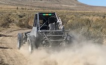 An off-road vehicle driving down a dirt road.