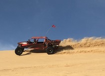 An off-road vehicle driving in the sand.