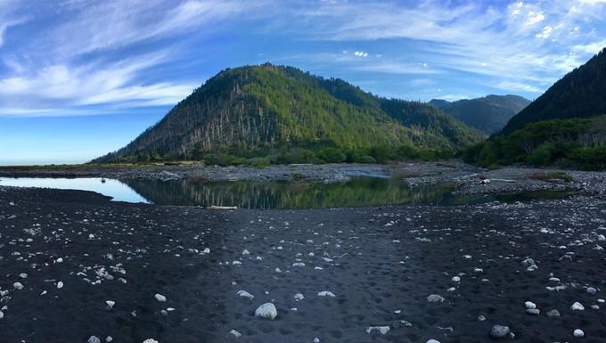 Mountain on the coast with a black sand beach.