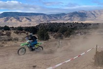 A motorcycle rider driving on a dirt trail with mountains in the background.