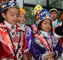 Several children dressed in Native American ceremonial clothes.
