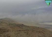 Smoke rising from a hillside.