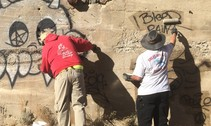Two people working to remove graffiti on a cement wall.