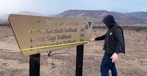 A BLM employee measuring a burned sign.