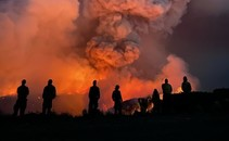 Silhouette of firefighters in front of a glowing fire.