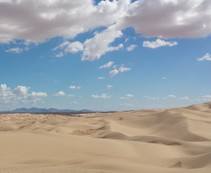 A vast landscape of sand dunes and a blue sky with white clouds.