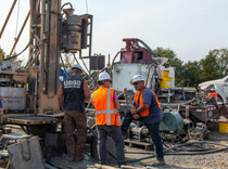 Workers stand near machinery