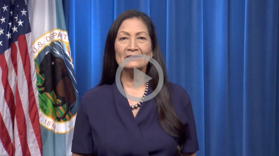 Secretary Haaland stands in front of a blue curtain with an American flag off to her side