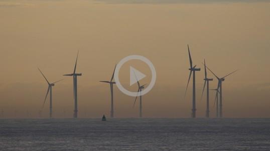Offshore wind turbines seen through a foggy ocean