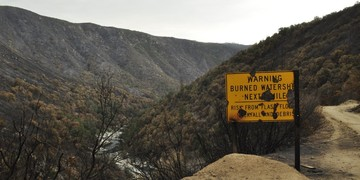A burned watershed warning sign that was burned in the Rim Fire marks the entrance to a damage area.
