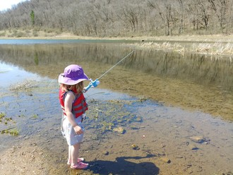 child looking at water in a pond while fishing