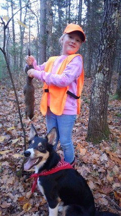 a female youth hunter shows off a squirrel harvested in the north Wisconsin woods