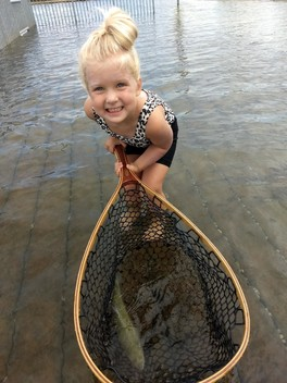 girl holding net with trout in bottom