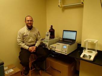 a man sitting on a stool next to lab equipment