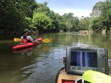 kayaks using side scan sonar in a river