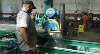 A worker cutting granite using a saw that applies water to the blade. The water reduces the amount of silica-containing dust that gets into the air.