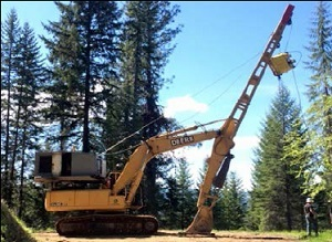 An excaliner with excavator pressed to the ground, used to maintain tension on the skyline. Photo courtesy of CDC/NIOSH/Oergon OSHA