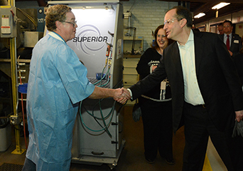 Secretary of Labor Alexander Acosta (right) meets with a worker at the Raytheon Precision Manufacturing facility in Dallas.