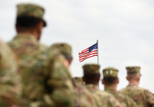 Photograph of soldiers looking at an American flag