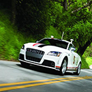 Image of race car racing down a tree-lined road.