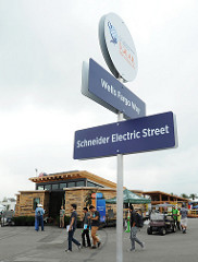 Photo of a street sign, including Wells Fargo Way, with people walking around a Solar Decathlon house beyond it.