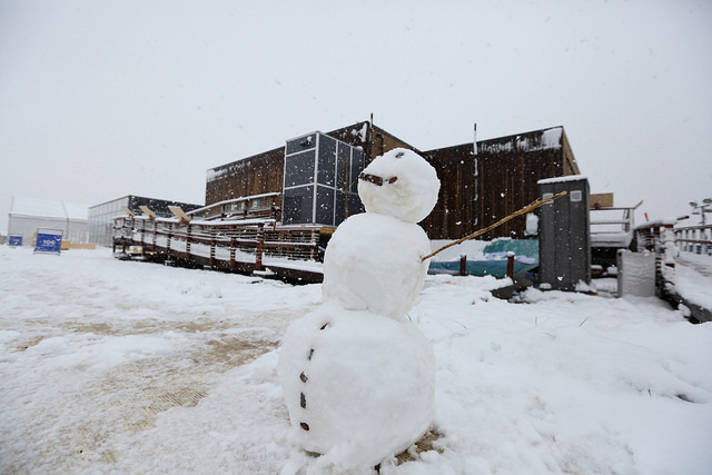 Photo of a snowman in front of a Solar Decathlon house.