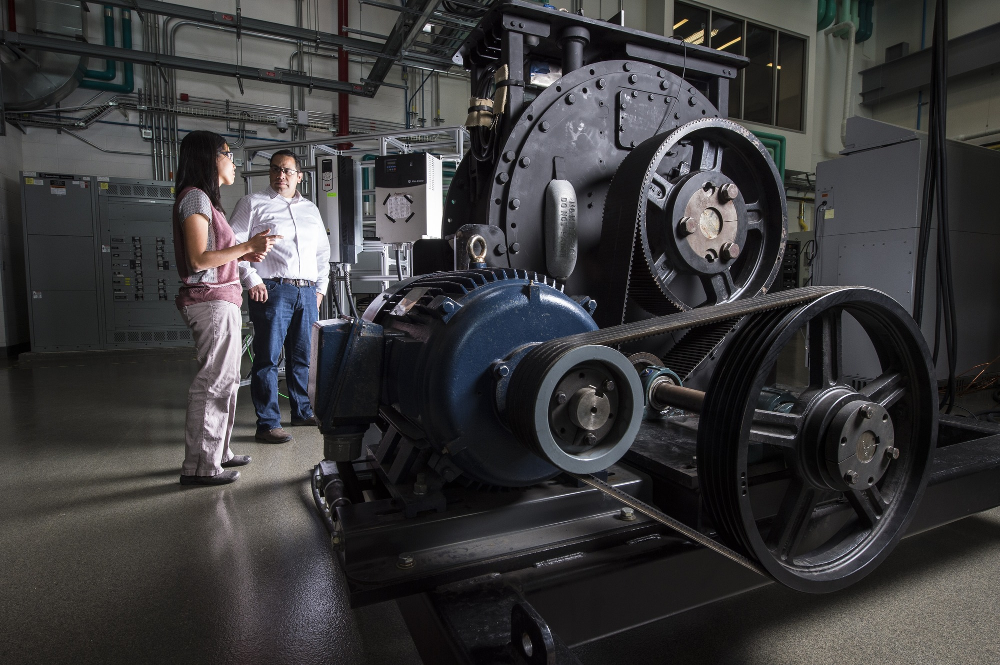 Two people  evaluating the performance of the generator and power conversion components of the company's RivGen® Power System at the ESIF.