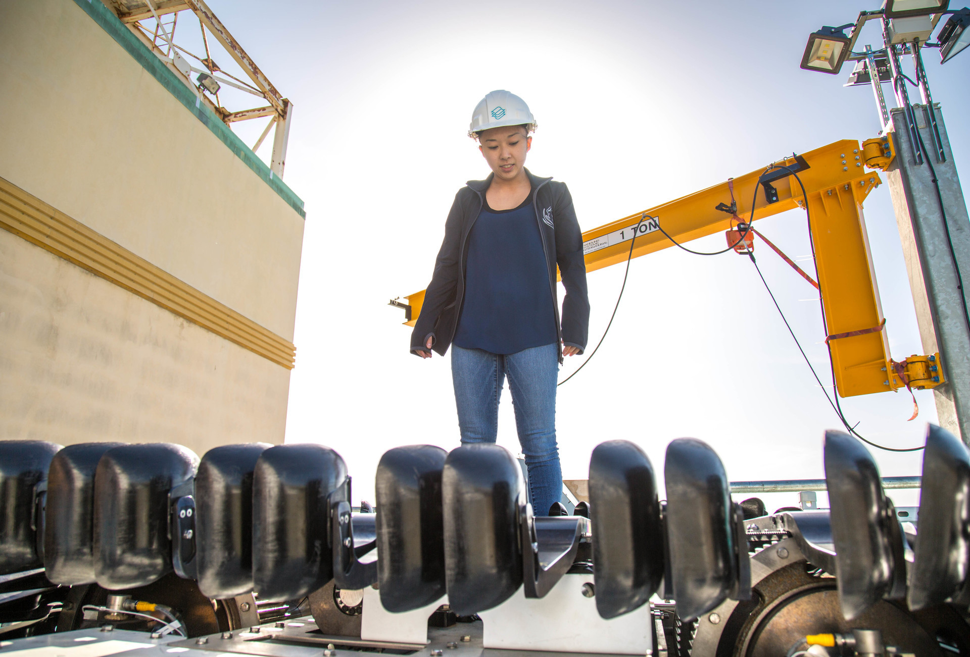 woman stands on a barge with a hardhat on.