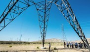 Group of people standing underneath electrical tower with one person in the middle looking straight up at it.