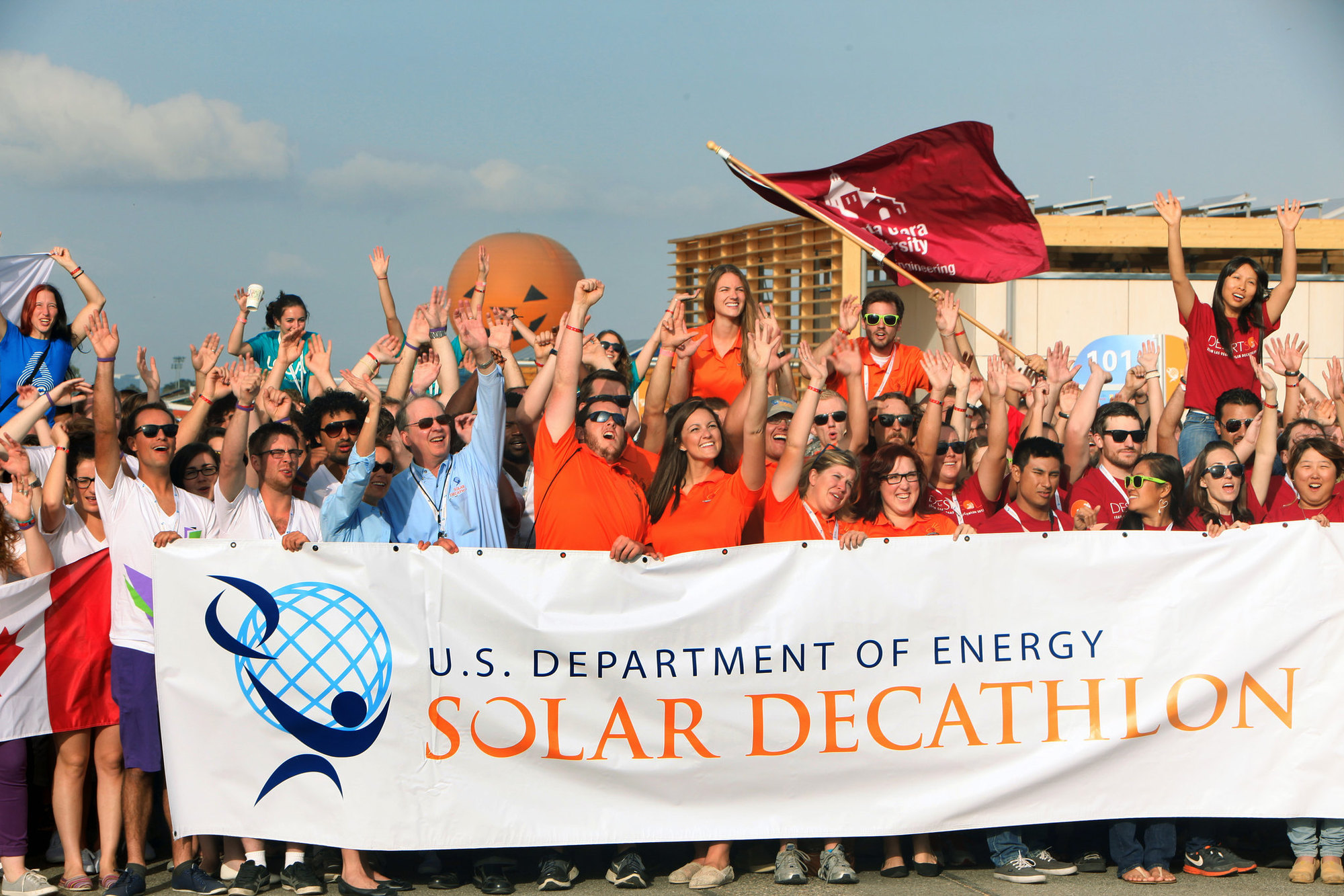 a photo of dozens of people holding a solar decathlon flag