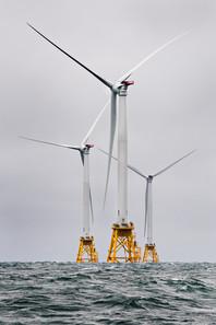 Three offshore wind turbines in a choppy sea.