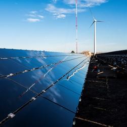 A wind turbine is reflected on a solar array.