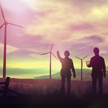 Two workers stand pointing at wind turbines.