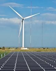 Wind turbine behind solar panels.
