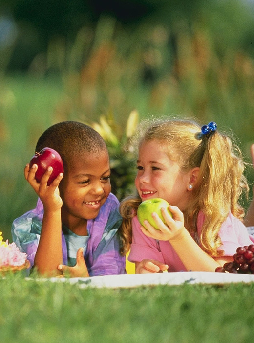 Boy and girl eating apples