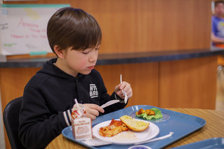 Boy eats school lunch