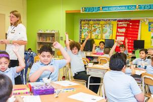 Kids in the classroom raising hands