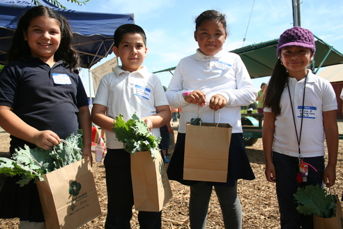 Kids holding produce bags