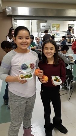 Two girls stand side-by-side as they show off their healthy snacks