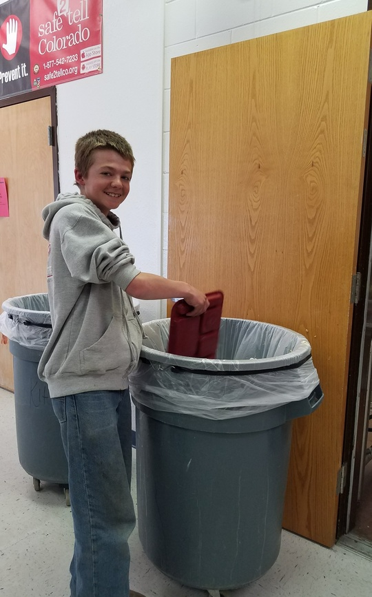 Boy dumps his lunch tray into a school cafeteria trash can