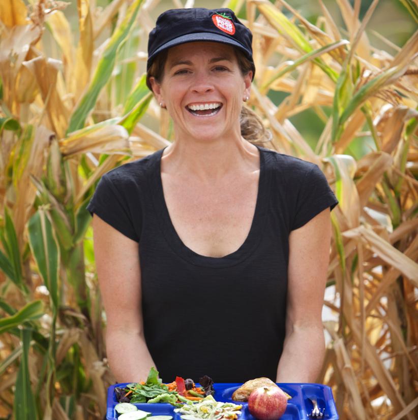 Woman holding a school lunch tray in corn field