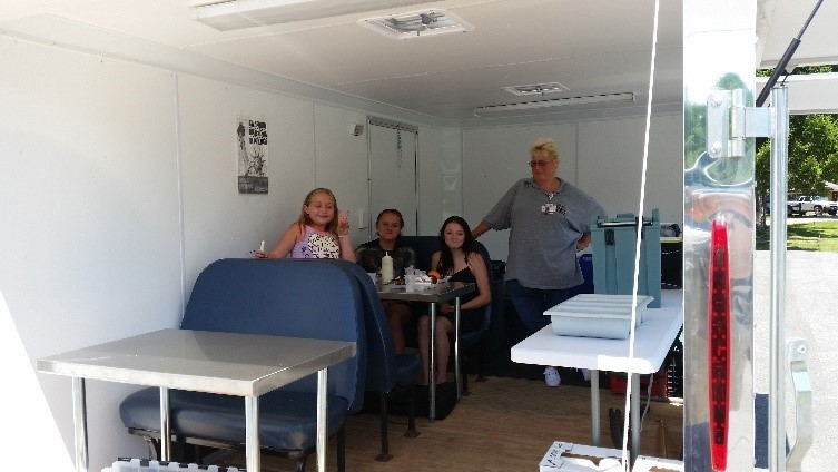 Children eat summer meals inside mobile trailer