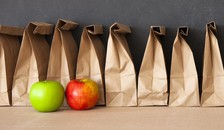 row of bag lunches and two apples on a table