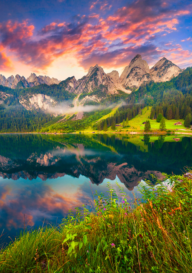 beautiful mountain scene with a pinkish sky and a glassy, reflective lake.