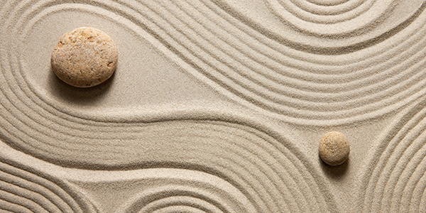 Sand with rocks carefully placed amongst lines formed into patterns by a zen raking.
