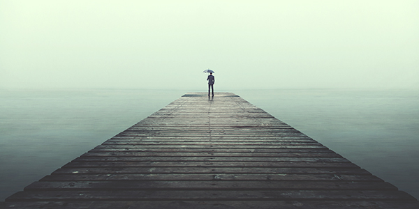 A person holding an umbrella, standing alone at the end of a pier with a greenish-grey cast over the water.